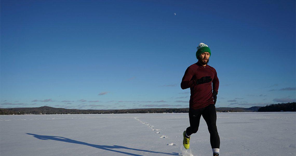 Mann mit Laufhandschuhen laeuft im Schnee