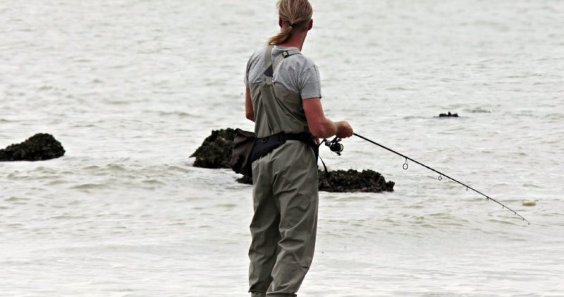 Mann mit Neopren Wathose angelt am Wasser