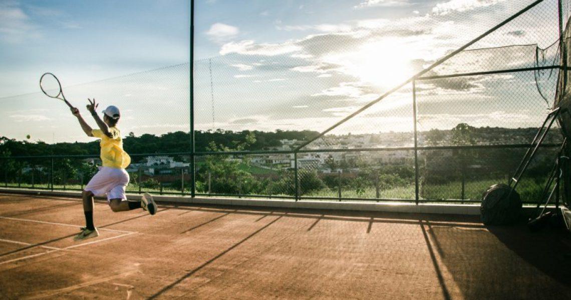 Ein Mann der mit einem Tennisschläger läuft