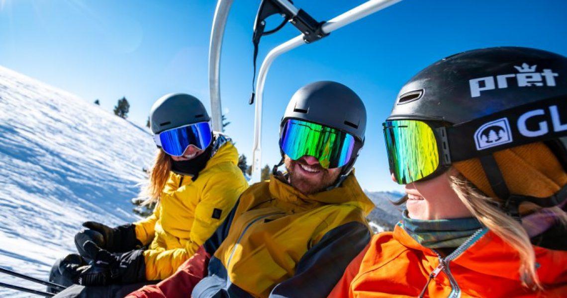 Skifahrer tragen Skibrillen und sitzen im Skilift.