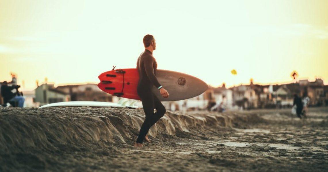 Ein Mann im Neoprenanzug trägt ein SUP-Board. Dies kann mit einer SUP Elektropumpe aufgepumpt werden.