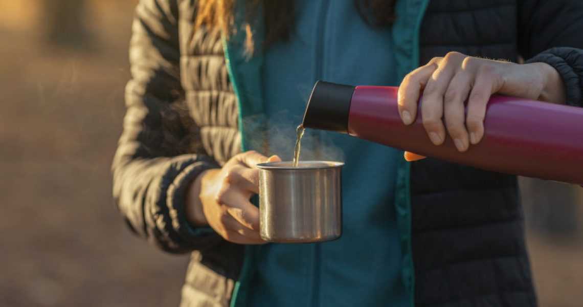Close up of woman hands pouring tea into camping mug