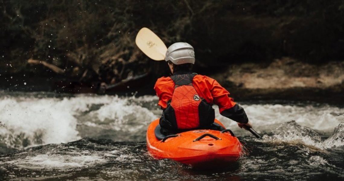 Wassersportler in einem Kajak Trockenanzug bei einer Kajaktour